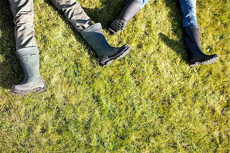 Low section of couple lying on grass Stock Photo - Premium Royalty-Free, Code: 698-07588178