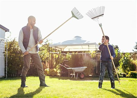 Father and son fighting with rakes at yard Stock Photo - Premium Royalty-Free, Code: 698-07588173