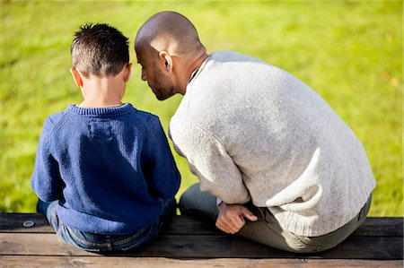 Rear view of father and son sitting at yard Stock Photo - Premium Royalty-Free, Code: 698-07588186