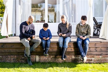 four - Family of four using mobile phones at yard Stock Photo - Premium Royalty-Free, Code: 698-07588183