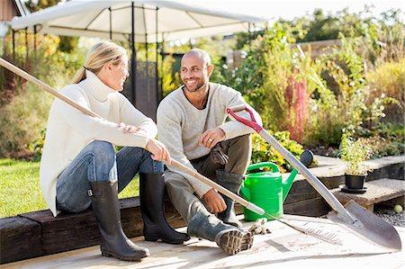 Full length of mature couple with gardening equipment sitting at yard Stock Photo - Premium Royalty-Free, Code: 698-07588191