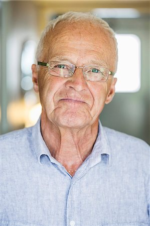 Portrait of confident senior man smiling indoors Stock Photo - Premium Royalty-Free, Code: 698-07588202