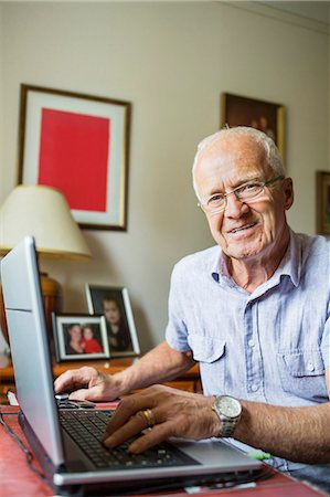 Portrait of smiling senior man using laptop at home Stock Photo - Premium Royalty-Free, Code: 698-07588213