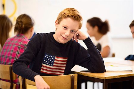 pennant flag - Portrait of confident schoolboy sitting at desk in classroom Stock Photo - Premium Royalty-Free, Code: 698-07588247