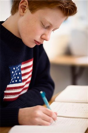 High school boy writing at desk in classroom Stock Photo - Premium Royalty-Free, Code: 698-07588241