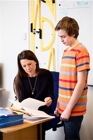 Teacher teaching high school boy at desk in classroom Stock Photo - Premium Royalty-Free, Code: 698-07588259