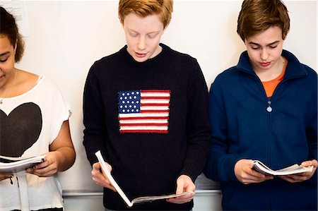 High school students reading book against whiteboard Stock Photo - Premium Royalty-Free, Code: 698-07588250