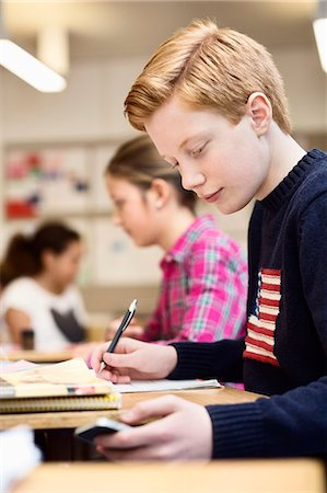 High school student using mobile phone while studying in classroom Stock Photo - Premium Royalty-Free, Code: 698-07588268