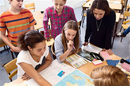 High angle view of teacher and students studying map at desk in classroom Stock Photo - Premium Royalty-Free, Code: 698-07588279