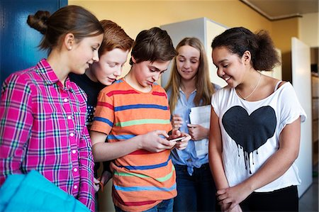 High school students using mobile phone in locker room Stock Photo - Premium Royalty-Free, Code: 698-07588288