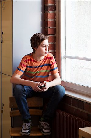 Thoughtful boy looking out through window in locker room at school Stock Photo - Premium Royalty-Free, Code: 698-07588280