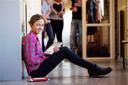 Side view portrait of happy schoolgirl sitting on floor in locker room Stock Photo - Premium Royalty-Free, Code: 698-07588296