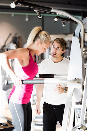 Instructor motivating customer exercising at gym Stock Photo - Premium Royalty-Free, Code: 698-07588307