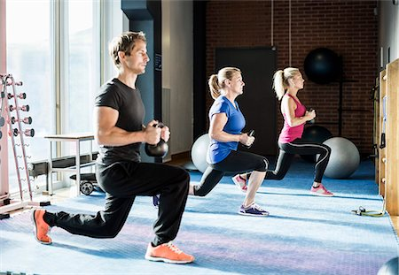Customers exercising with kettlebells at gym Stock Photo - Premium Royalty-Free, Code: 698-07588327