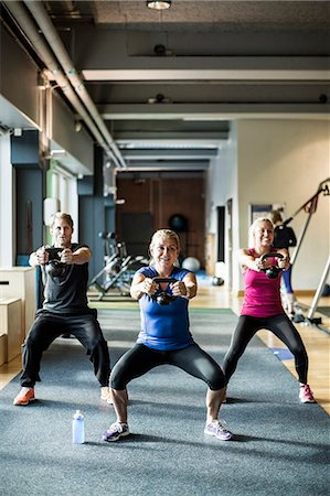 Full length of friends lifting kettlebells at health club Stock Photo - Premium Royalty-Free, Code: 698-07588328
