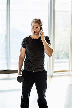 Man using mobile phone while exercising at gym Stock Photo - Premium Royalty-Free, Code: 698-07588329