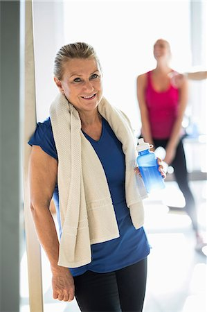 Portrait of fit senior woman with towel and water bottle standing at gym Stock Photo - Premium Royalty-Free, Code: 698-07588321
