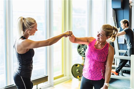 Fit women fist bumping at health club Stock Photo - Premium Royalty-Free, Code: 698-07588339