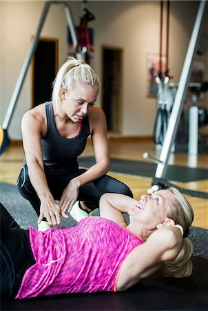 Female instructor assisting senior woman in doing sit-ups at gym Stock Photo - Premium Royalty-Free, Code: 698-07588331