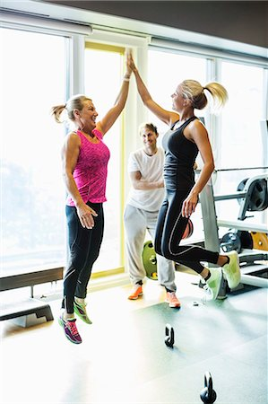 Excited fit women giving high-five at gym Stock Photo - Premium Royalty-Free, Code: 698-07588342
