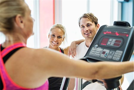 Friends looking at woman exercising on treadmill at gym Stock Photo - Premium Royalty-Free, Code: 698-07588343