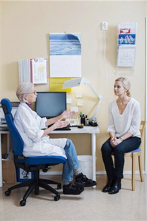 Full length of senior female doctor talking with woman in clinic Stock Photo - Premium Royalty-Free, Code: 698-07588450