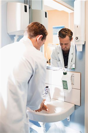 Rear view of male doctor washing hands in bathroom Stock Photo - Premium Royalty-Free, Code: 698-07588466
