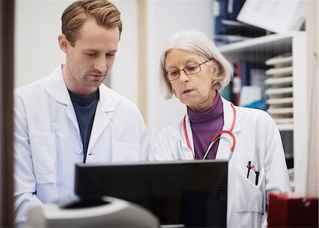 Senior female doctor with male colleague using computer in examination room Stock Photo - Premium Royalty-Free, Code: 698-07588460