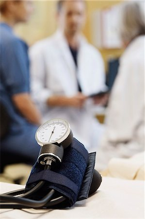 Blood pressure gauge with medical team discussing in background Stock Photo - Premium Royalty-Free, Code: 698-07588476