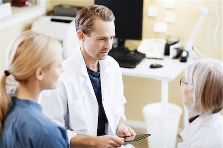 Doctors and nurse with digital tablet discussing in hospital Stock Photo - Premium Royalty-Free, Code: 698-07588473