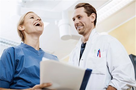 Happy doctor with nurse holding report in hospital Stock Photo - Premium Royalty-Free, Code: 698-07588483