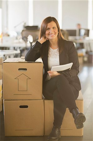 Portrait of confident businesswoman sitting on cardboard box in new office Stock Photo - Premium Royalty-Free, Code: 698-07588505