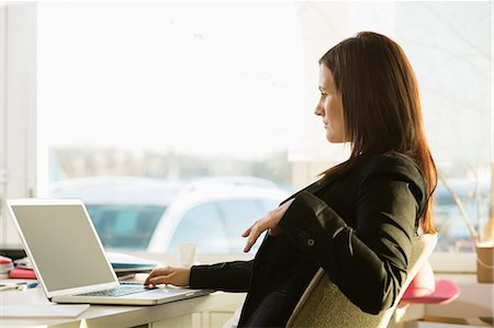 Side view of businesswoman working on laptop at desk Stock Photo - Premium Royalty-Free, Code: 698-07588513