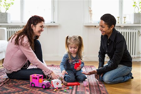 Happy lesbian couple playing with girl at home Stock Photo - Premium Royalty-Free, Code: 698-07588534