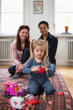 Lesbian couple looking at girl playing with toys in living room Stock Photo - Premium Royalty-Free, Code: 698-07588535