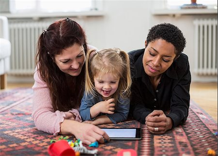 Smiling lesbian couple and girl using digital tablet at home Stock Photo - Premium Royalty-Free, Code: 698-07588536