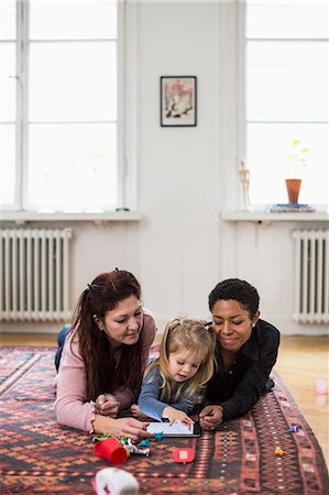 Girl and lesbian couple using digital tablet in living room Stock Photo - Premium Royalty-Free, Code: 698-07588537