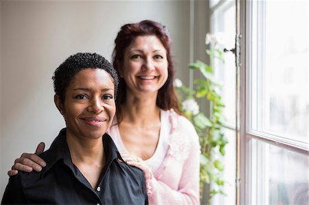 Portrait of smiling lesbian couple by window at home Stock Photo - Premium Royalty-Free, Code: 698-07588539