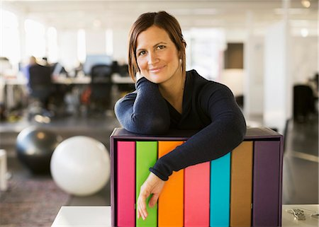 Portrait of confident businesswoman leaning on folder rack in office Stock Photo - Premium Royalty-Free, Code: 698-07588531