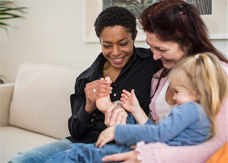 Happy lesbian couple with girl in living room Stock Photo - Premium Royalty-Free, Code: 698-07588533
