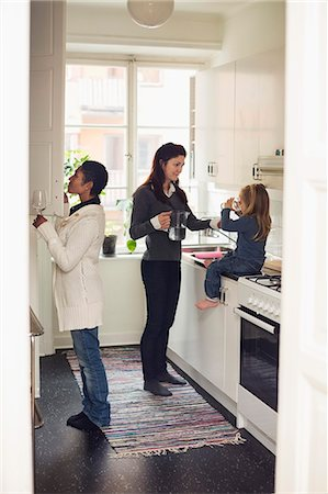 Full length of lesbian couple with girl in kitchen Stock Photo - Premium Royalty-Free, Code: 698-07588541