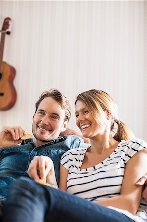 Happy couple having snacks while watching TV Stock Photo - Premium Royalty-Free, Code: 698-07588607