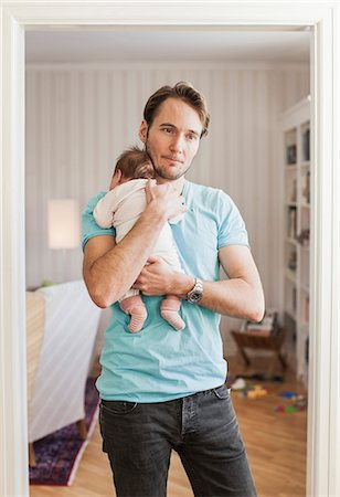 Thoughtful man carrying baby at doorway Stock Photo - Premium Royalty-Free, Code: 698-07588600