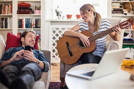 Happy woman playing guitar for man at home Stock Photo - Premium Royalty-Free, Code: 698-07588611