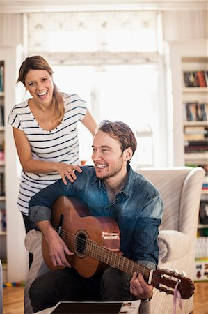 Happy man playing guitar for woman in house Stock Photo - Premium Royalty-Free, Code: 698-07588613