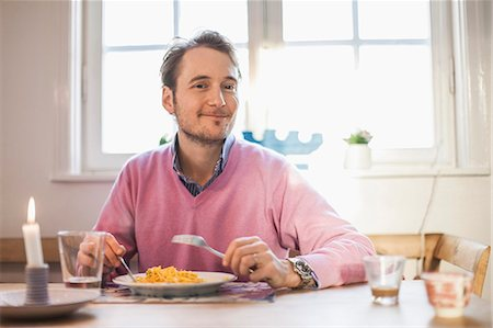 people eating at lunch - Portrait of man smiling while eating pasta Stock Photo - Premium Royalty-Free, Code: 698-07588627