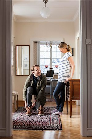 domestic life - Man wearing shoes while looking at woman in house Stock Photo - Premium Royalty-Free, Code: 698-07588623