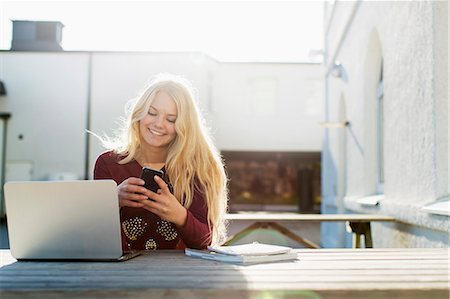 Happy teenage girl using mobile phone with laptop on table outdoors Stock Photo - Premium Royalty-Free, Code: 698-07611420
