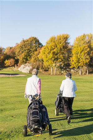 Rear view of senior women walking with golf bags on course Stock Photo - Premium Royalty-Free, Code: 698-07611456