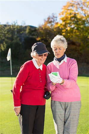 Senior female golfers using mobile phone on golf course Stock Photo - Premium Royalty-Free, Code: 698-07611458